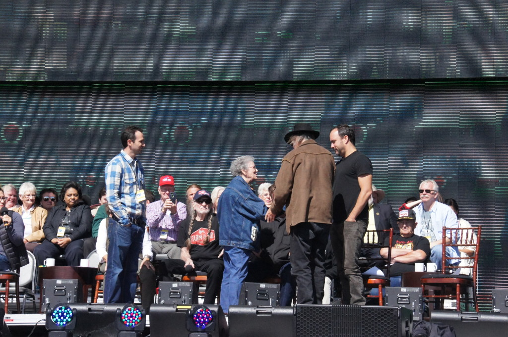 Neil Young (brown jacket) and Dave Matthews (black shirt) greet Mona Lee Brock of Oklahoma, whose life-saving efforts with the suicide prevention crisis hotline she started during the farm economic crisis of the 1980s were highlighted during the Farm Aid events in Chicago. The farm crisis prompted the establishment of the Farm Aid organization in 1985.