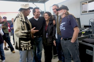 Carolyn Mugar (center) has been executive director of the Farm Aid organization since just after its beginning in 1985. Here, she is surrounded by Farm Aid board members (left to right) Neil Young John Mellencamp, David Matthews and Willie Nelson at the Farm Aid concert in Seattle in 2004. - September 18th, 2004 White River Ampitheater Seattle, Washington United States September 18th, 2004. Photo: ©Paul Natkin/WireImage.com
