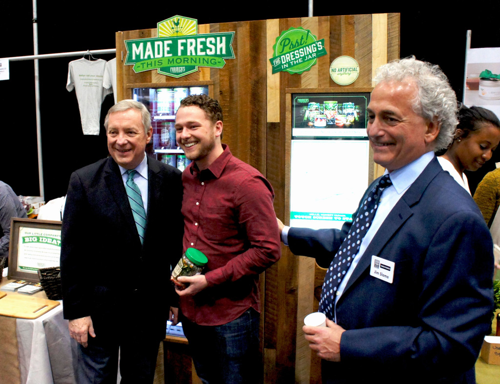 Farmer's Fridge founder Luke Saunders (center) credits his participation in FamilyFarmed's annual Good Food Festival & Conference and its Financing Fair with helping him scale his business up quickly. Here he enjoyed a visit by Illinois U.S. Sen. Dick Durbin (left) and FamilyFarmed President Jim Slama at the 2015 Good Food Festival & Conference.