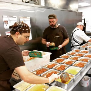 Employees of The Foodery in Boston prepare meals for delivery.