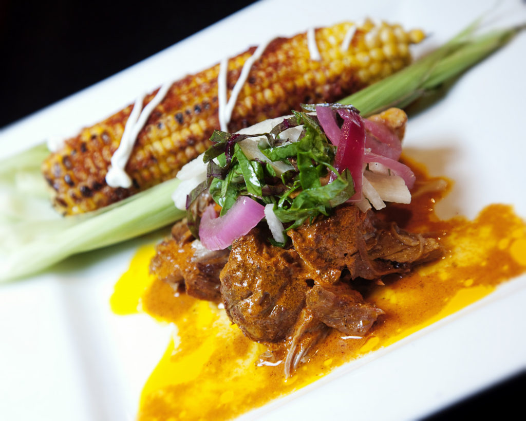 The Mayan Café's Conchinita Pibil is made with pork (from two local producers), achiote sauce, the restaurant's signature lima beans, served with a Yucatec tamale of roasted corn. The cuisine is based strongly on the traditional cooking of Chef Bruce Ucán's native Yucatan Peninsula in Mexico.
