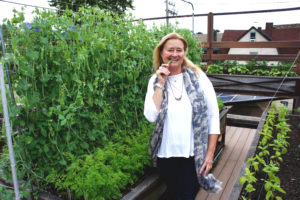 Helen Cameron, who co-founded Uncommon Ground with her husband Mike 25 years ago, snacks on a sugar snap pea grown at their restaurant that has the nation's first certified organic rooftop farm. Photo: Bob Benenson/FamilyFarmed