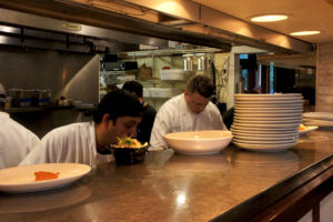 Chef-owner John DesRosiers (right) in the open kitchen at Inovasi. Photo: Bob Benenson/FamilyFarmed