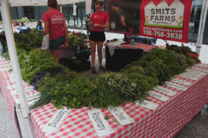 Smits Farm — which sells at several Chicago farmers markets, including this one at Federal Plaza — is a price leader. Those big bunches of herbs and greens go for between $1 and $2 apiece. Photo by Bob Benenson/FamilyFarmed.