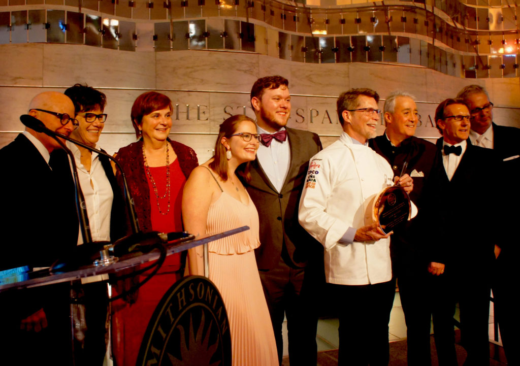 "Rick Bayless, surrounded by family, friends and presenters, holds his Julia Child Award — modeled on one of Child's signature copper pans — under a dramatic metal sculpture of the U.S. flag at the Smithsonian Institution's Museum of American History Oct. 27. ""It's hard for me to even be in this museum, because it's palpable, the history of this great country all around you,"" Bayless said in his speech. ""Not palpable in big things, but in little things in people's lives, and that's what we do when we share food with people."""