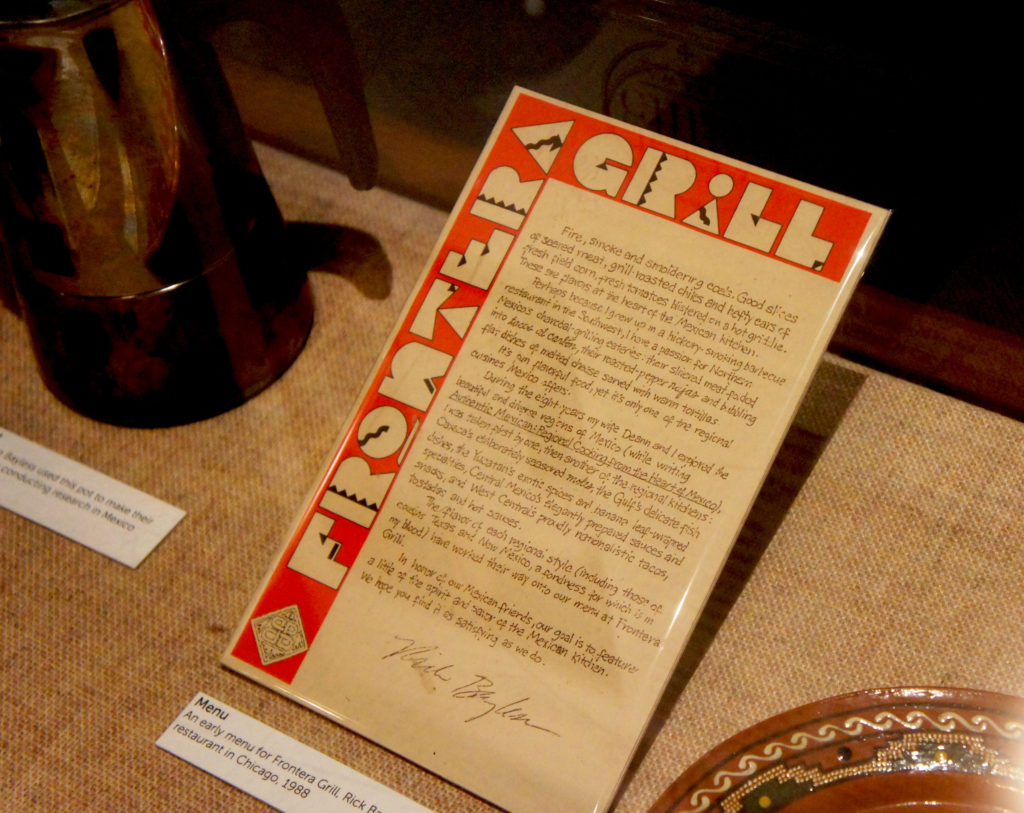 Artifacts donated by Rick Bayless from his career popularizing regional Mexican cuisine in the U.S. are displayed in a showcase next to Julia Child's kitchen in the Museum of American History. They included one of the notebooks in which he meticulously documented his research on Mexican food (far left in the showcase) and a menu from Chicago's Frontera Grill in 1988, a year after it opened.