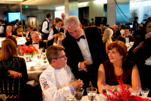 FamilyFarmed founder and president Jim Slama chats with honoree Rick Bayless and Deann Bayless, his wife and business partner, during the Julia Child Award dinner Oct. 27.
