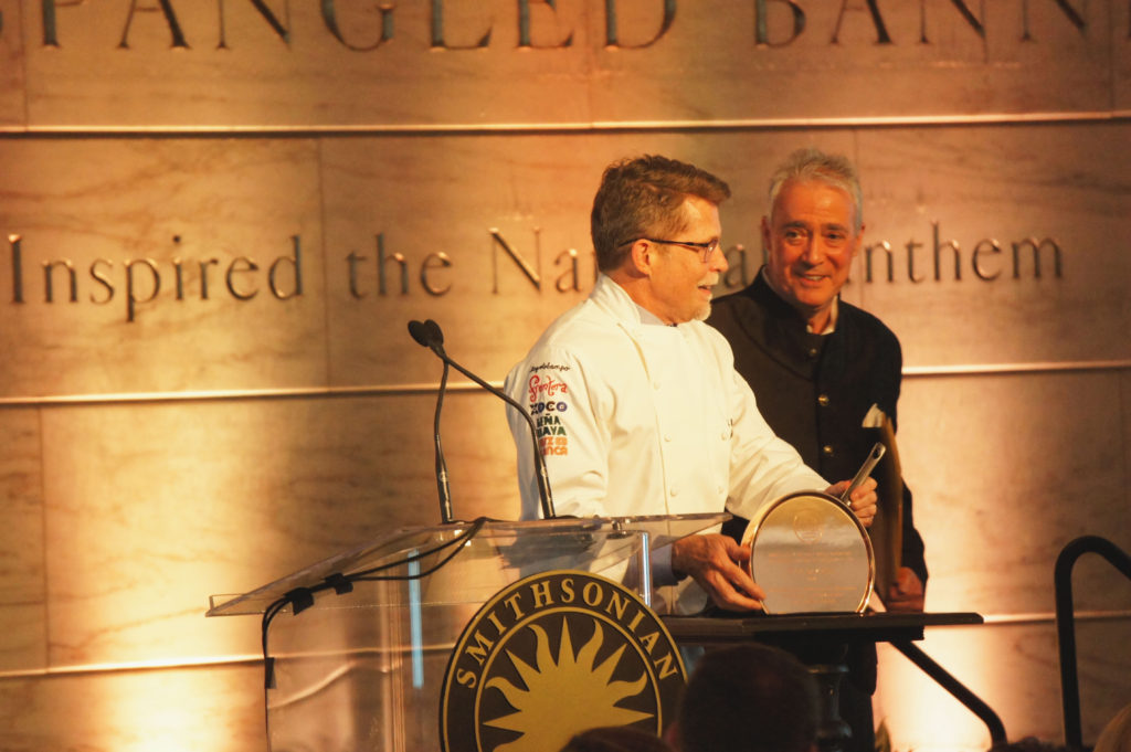 Rick Bayless poses with his Julia Child Award — fashioned after one of the namesake's trademark copper pans — as Scott Simon of National Public Radio looks on. Simon introduced Bayless, a close personal friend, at the event.